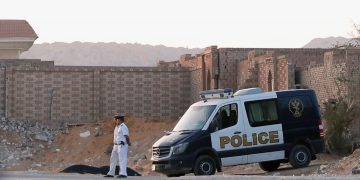 Policemen guard outside the cemetary where ousted Egyptian Islamist President Mohamed Mursi was buried early morning in Cairo