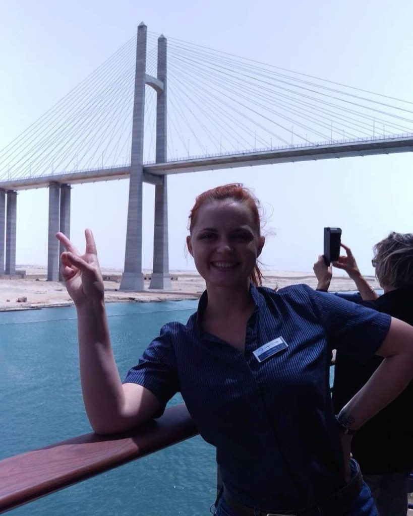A girl points with his two fingers with Suez Canal Bridge