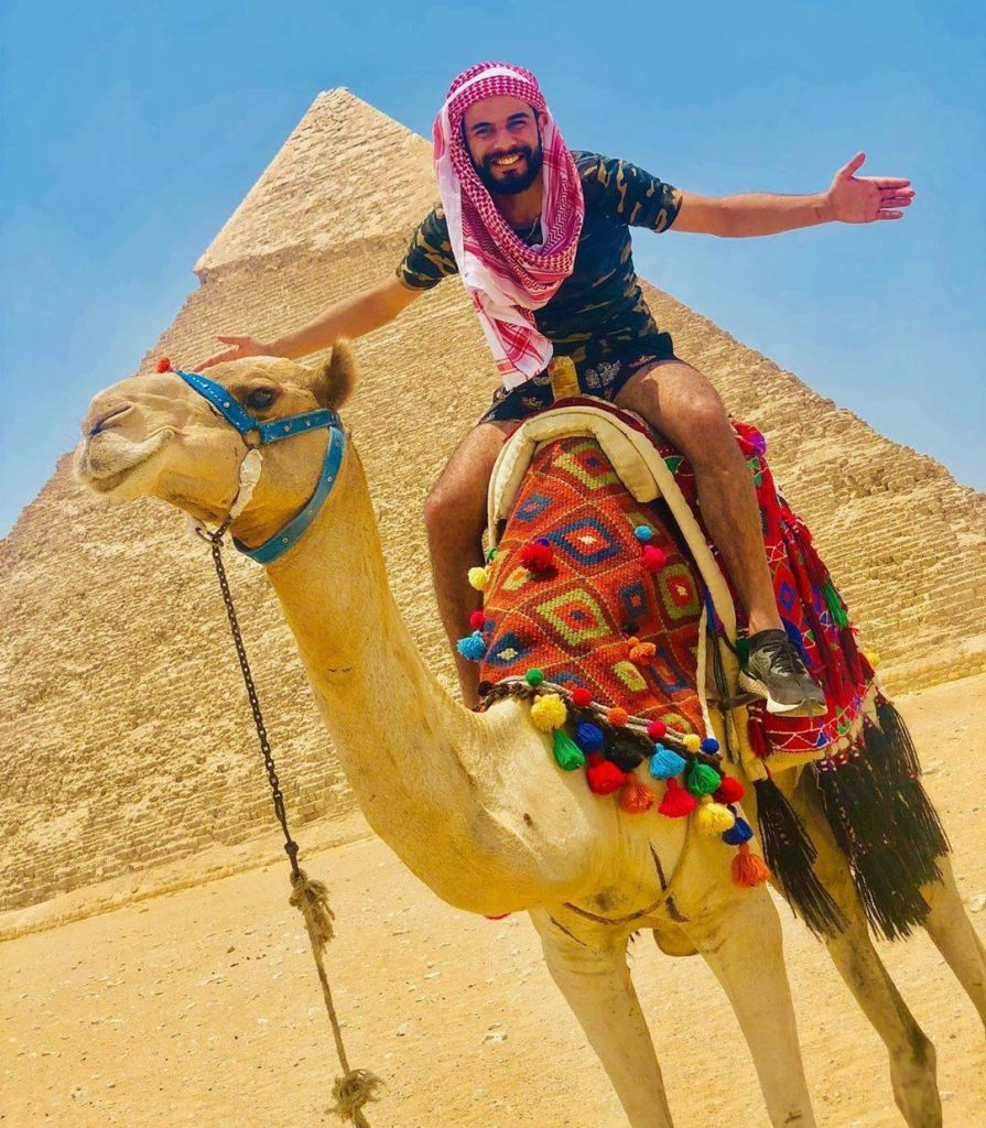 A man rides a camel next to Pyramids