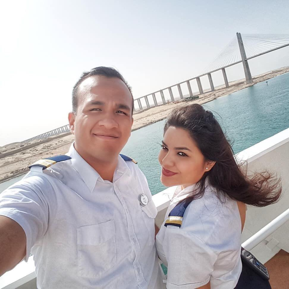 A man and woman take selfie with the bridge