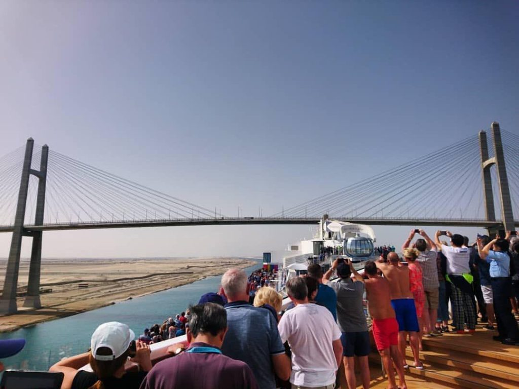 A group of tourists look to Suez Canal Bridge