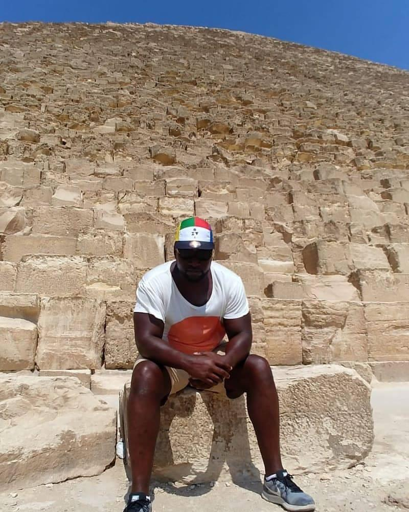 A fan sets on a stone next to a pyramid