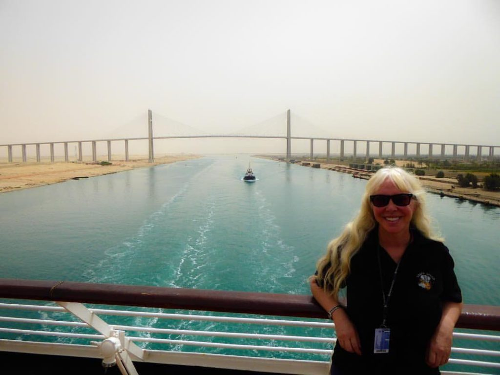 The photo shows water in Suez Canal and its bridge in the background