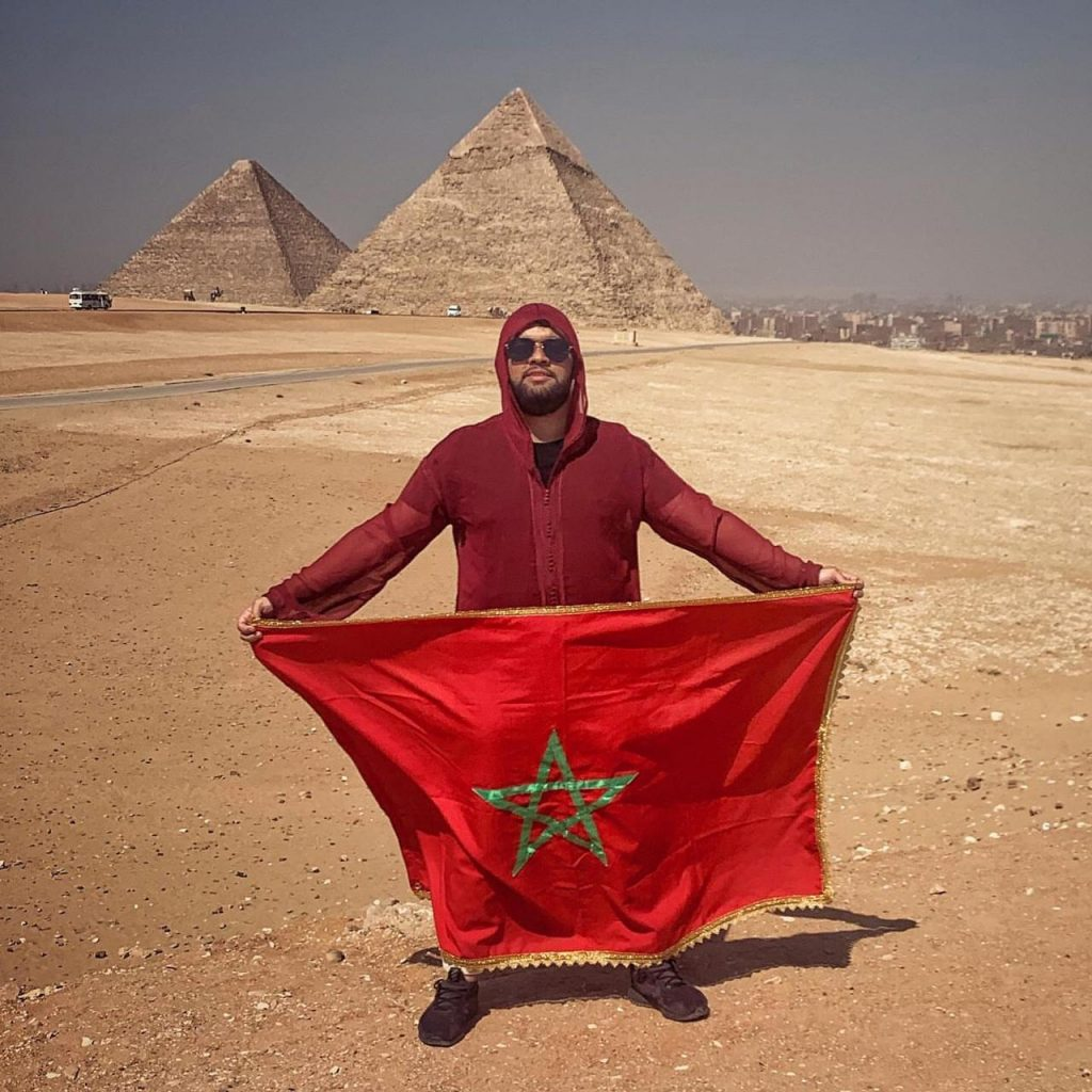 Tunisian man takes photo with her country`s flag in front of Giza pyramids