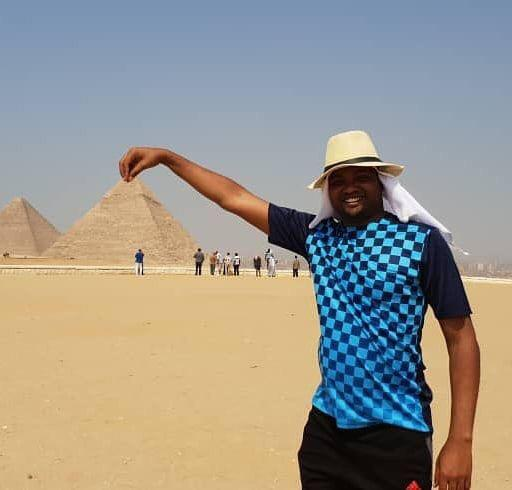 A man takes funny photo with a pyramid