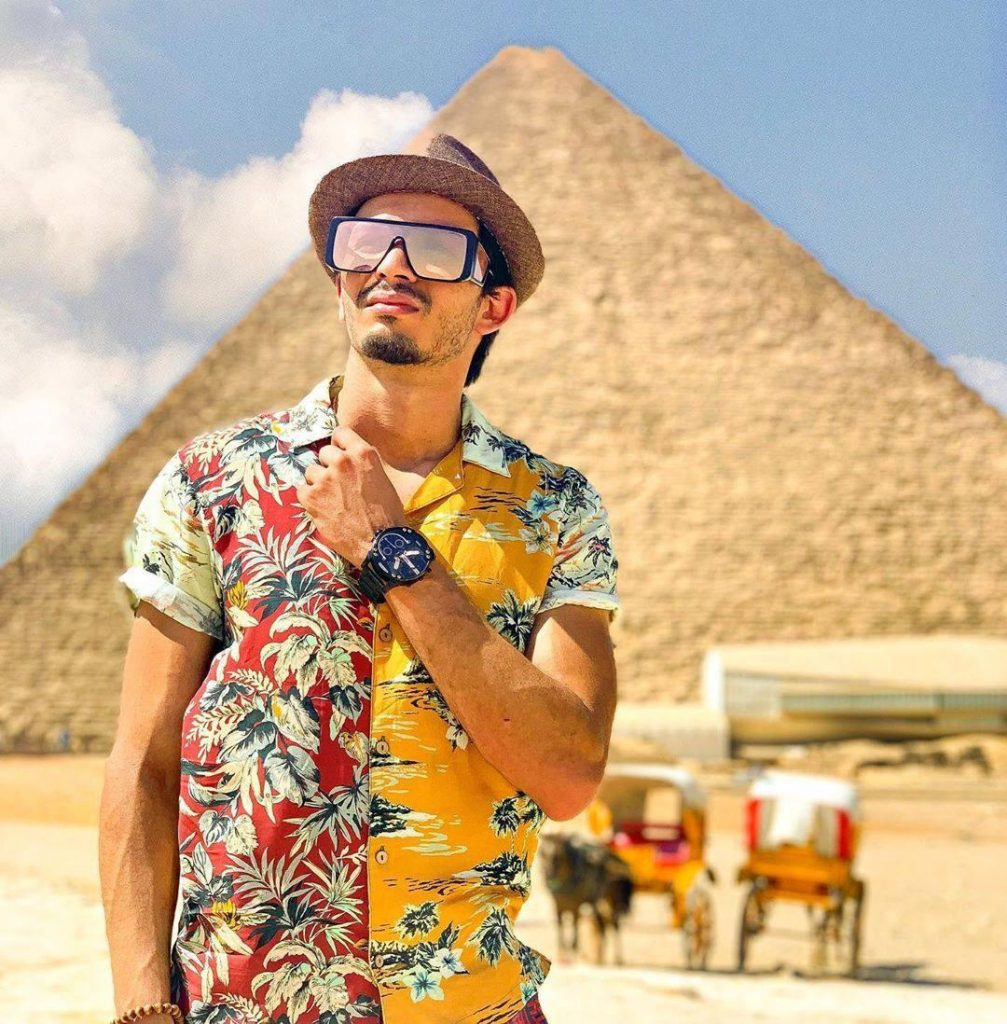 A man in front of a pyramid