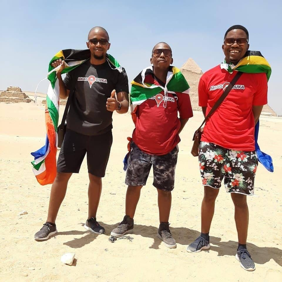 Three men carry their country`s flag in front of Pyramids
