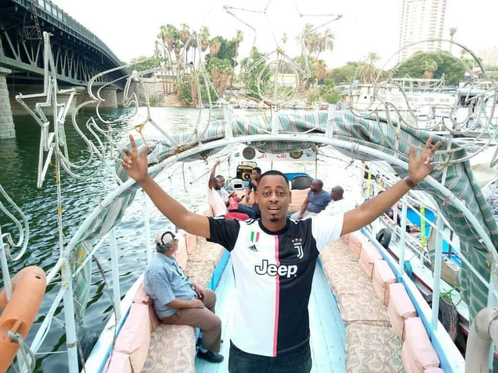 An African fan takes photo in the Nile River