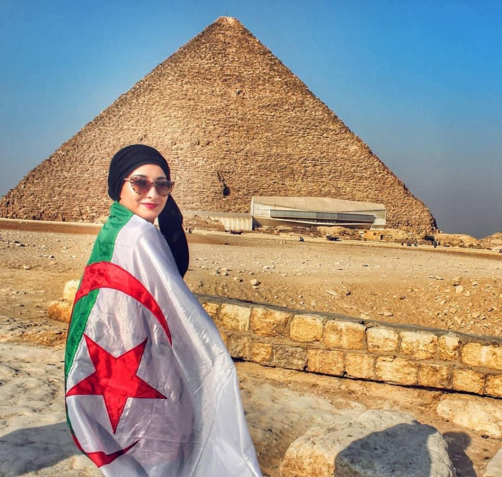 Algerian girle takes photo with the pyramids