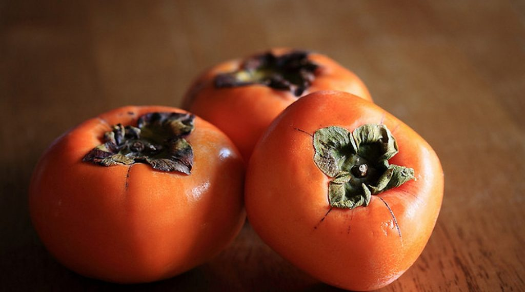 Three Persimmons on A Wooden Table